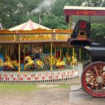 The carousel in the background with a traction engine in front