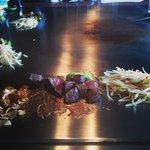 Presentazione della carne cucinata e servita a pezzetti, accompagnata da fettine di aglio