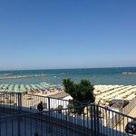 a dx la spiaggia dell'hotel con gli ombrelloni beige piuttosto ammassati rispetto allo standard,