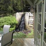 Waterfall alongside cottage, koi pond past bridge.