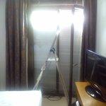 La habitación decorada con una persiana rota y una escalera.