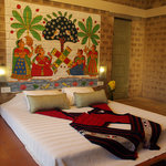 A bedroom with a wall mural painted by tribal/rural artists
