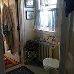 Shared bathroom with door left open to private bedroom beyond