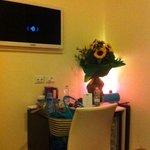 particolare stanza con desk, tv e lampada fucsia