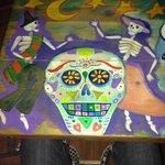 "Art work on the table we sat at (im assuming representing ""Dia de Muertos"""