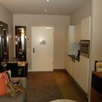 Entrance to the room. Kitchenette on right and table on left