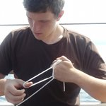 First Mate Cyrus making a nautical bracelet
