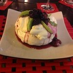 Mini Pavlova served with fresh fruit and berry sauce