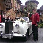 Rolls Royce Hochzeitsauto unter dem Rosenspalier des Personals