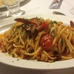 Lobster hidden amongst flat spaghetti and cherry tomatoes