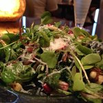 Organic Baby Kale Salad in a garlic and mustard seed vinaigrette, pomegranates, watermelon radis