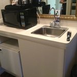 Cute little sink with the microwave and refrigerator