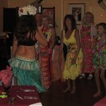 The Hula girl demonstrates some moves to some restaurant patrons.