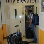 tiny elevator - two people, two suitcases