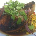 Pork chop with succulent corn dish bed.