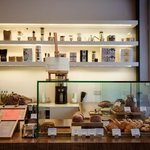 Display with a variety of pastries and retail coffee and tea equipment.