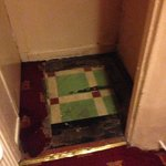 entrance to ladies square of rotting carpet cut away
