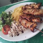 Marinated chicken skewers served on a bed of cous cous and accompanied by coleslaw and salad.