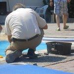 L'homme à tout faire qui répare l'éclairage de la piscine en plein milieu de la journée