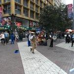 Santiago de Chile. Paseo Huérfanos con Paseo Ahumada. Organillero y Chinchineros bailando.