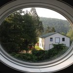 Oval window in the bathroom frames a country view