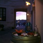 Sun setting beyond the arch from outside table at Le Tout du Cru