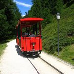 A red nice trolley carries visitors from the train station to the resort