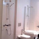 Strange shower, no curtain, but also a shower in bathtub