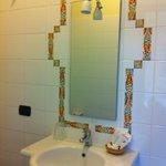 Dettaglio cornice bagno decorata con tessere d'artigianato locale
