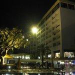 O hotel á noite com a piscina