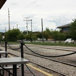 Picnic tables by the rails on a historic train depot platform, nice!
