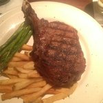 20-22 oz Bone-In Ribeye with Steamed Asparagus and French Fries.