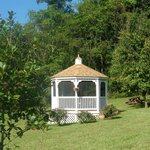 Screened gazebo on property is lit at night.