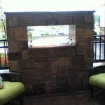 Outside fireplace next to breakfast area with tables and chairs