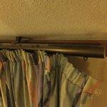 Verschmutzte Gardinenstange und abgerissener Vorhang