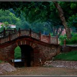 a picturesque bridge adds to the charm of the pretty gardens