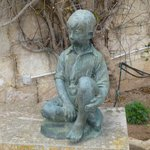 A nice statue of a boy in a corner of the garden.