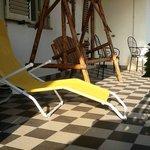Terrazzo attrezzato con sdraio, dondolo, sedie e tavoli per sterni