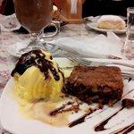 Un brownie tibio con helado y un chocolate caliente