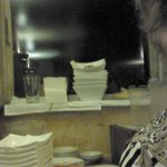 The table behind me with clean and dirty plates stacked nexy to each other, nexy to the bread an
