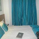 Quarto com roupa de cama e cortina azul