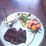 exquisito plato en su punto exacto de la decoración acopañadada por verduras a la brasa extras y
