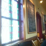 Chalk board beer list next to the stain glass window