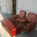 A set of worn desk and chairs outside..for visitors?