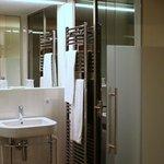 Badezimmer durch Stahl und Glas vom zimmer abgetrennt