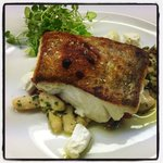 Pan fried cod on haricot beans, crispy bacon & goats cheese