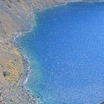 The caldera water turns turquoise as it comes in contact at the hill's foot...