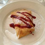 Crepe filled with peaches and vanilla ice cream, drizzled with raspberry