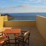 Balcony with table and chairs overlooking the Aegean