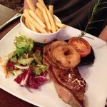 Steak with chips and couple onion rings to the side mushroom cap and tomato and small salad